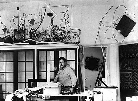 Alexander Calder in his shop with kinetic sculptures and materials